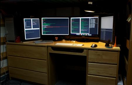 Большой компьютер с четырьмя мониторами на большом столе